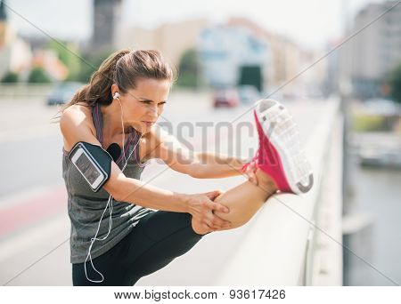 Woman Runner Stretching Leg On Rail In Summer In Urban Setting