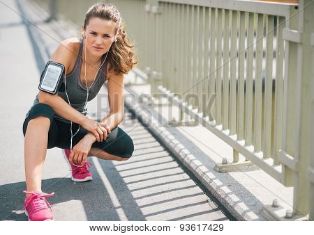 Woman Runner Kneeling On Sidewalk In Summer In Urban Setting