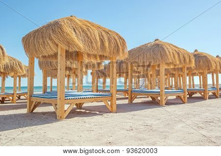Beach With Thatched Gazebo And Sun Loungers