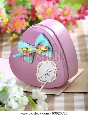 heart shaped gift with bow on flower background