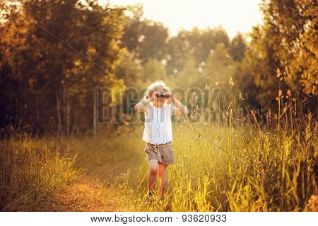child girl watching birds with binoculars in summer forest
