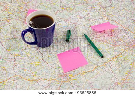 Blue coffee mug and paper with ballpoint on map, preparation for travel