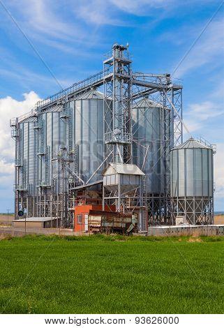 Industrial silos under blue sky, in the field