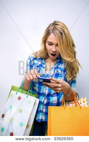 Girl teenager looking smartphone and holding shopping bags