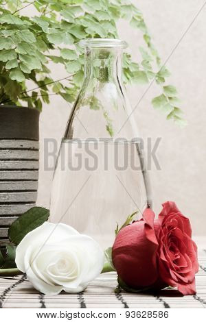glass bottle with eau de toilette and white and red roses