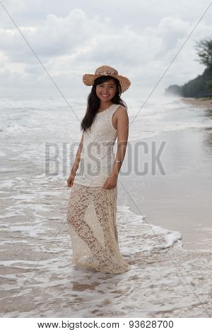 Portrait Of Smiling Face Of Young Asian Woman With Long Dress And Fashion Wide Straw Hat Standing On