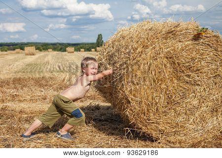 Boy Pushes Bale Of Straw