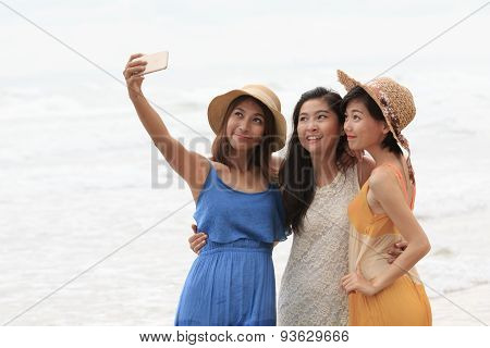 Portrait Of Asian Young Beautiful Woman Wearing Long Dress Standing On Sea Beach Taking A Photograph