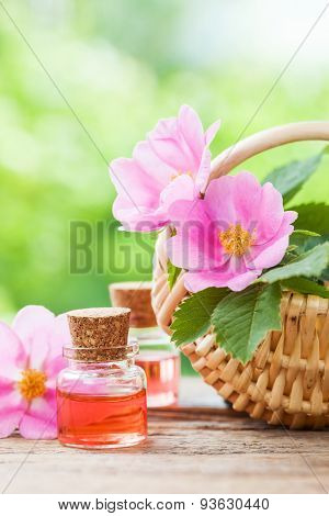 Rustic Wicker Basket With Rose Hip Flowers And Bottles Of Essential Oil On Old Wooden Table