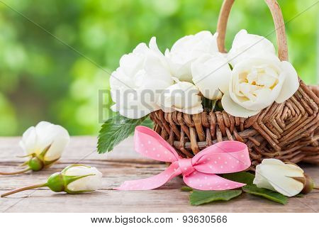Rustic Wicker Basket With Wild Rose Flowers And Pink Ribbon.