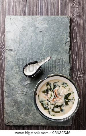 Creamy Soup With Eel And Spoon On Stone Slate Background