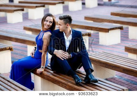 young couple in park bench on a summer day