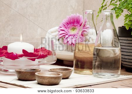 bowl with water and rose petals and bottle with essential oils