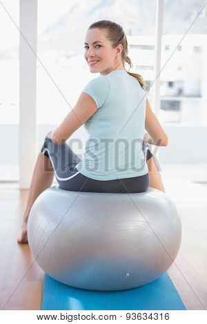 Woman looking at camera and sitting on exercise ball in fitness studio