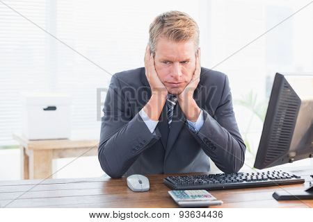 Depressed businessman at his desk in his office