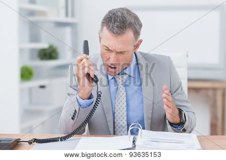 Irritated businessman answering phone in his office