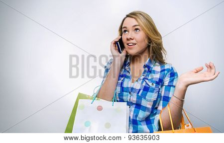 Girl teenager talking by smartphone and holding shopping bags