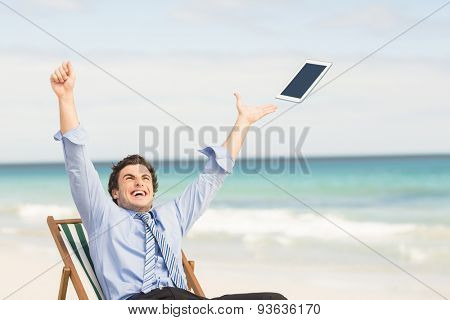Businessman launching his tablet computer on the beach