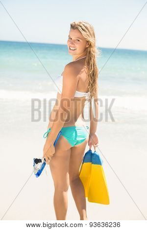 Happy pretty blonde holding mask, scuba and fins at the beach