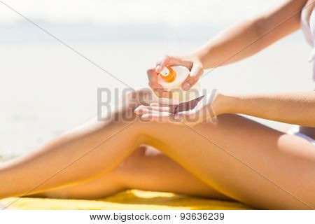 Close up view of Pretty blonde woman putting sun tan lotion on her hand at the beach