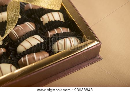 Close up of fine quality date chocolates in a golden gift box. Partial view.