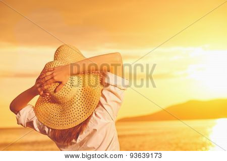 Beauty Happy Woman In Her Hat Is Back And Admire Sunset Over Sea On Beach