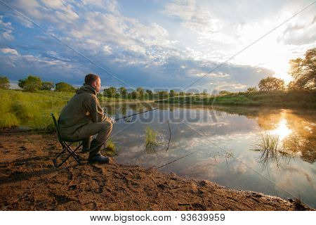 Fisherman With Fish-rod In His Hands Near A Pond
