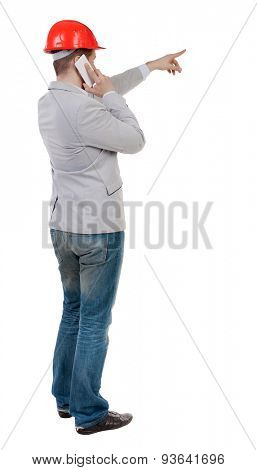 Backview business man in construction helmet stands and enjoys tablet or using a mobile phone.  backside view of person.  Isolated over white background. manager on a construction site runs on phone