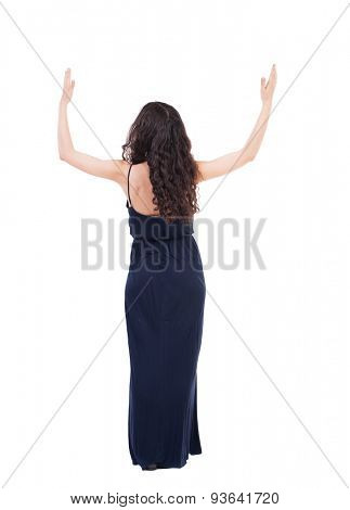 Back view of Beautiful woman in dress looking at wall and Holds  hand up. young blonde girl standing. Isolated over white background. Young woman in prayer. Girl in a blue evening dress is praying god