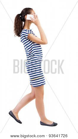 a side view of woman walking with a mobile phone. beautiful curly girl in motion.  backside view person.  African-American woman in a striped dress on the move enthusiastically talking on the phone