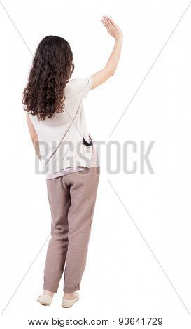 Back view of curly woman welcomes. Young teenager girl hand waving from. Rear view  people collection.  backside view of person.  Isolated over white background. Curly girl waving good-bye.