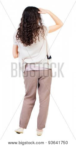 back view standing young beautiful  woman. girl  watching. Rear view people collection. backside view person.  Isolated over white background. girl with curly hair looking palm covering eyes from sun.