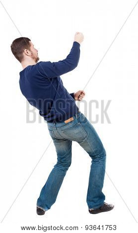 back view of standing man pulling rope from top or cling to something. guy watching. Rear view people collection. Isolated over white background. Man in jeans and blue sweater pulls the rope on top