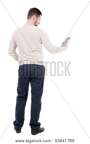 back view of standing young man with tablet computer in the hands of. Rear view people collection.  backside view person. Isolated over white background. bearded man in black trousers looks at plate.