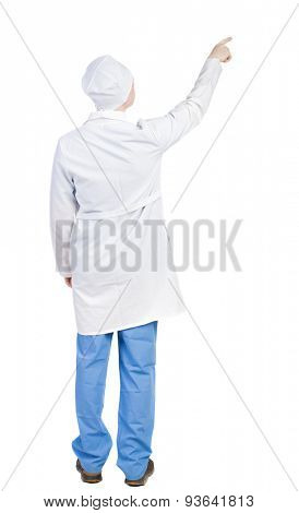 Back view doctor in robe pointing. Standing young guy. Rear view people collection.  backside view person. Isolated over white background. doctor in dressing gown shows finger on something that tells.