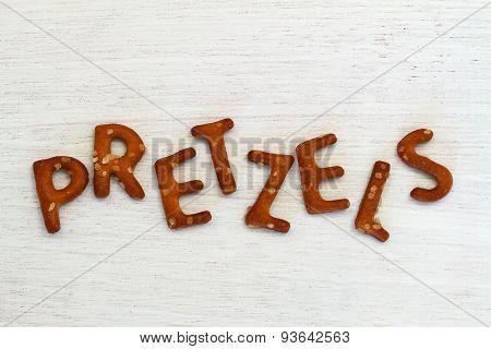 Word pretzels written with pretzel-like letters on white wood