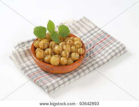 bowl of stewed gooseberries on checkered dishtowel