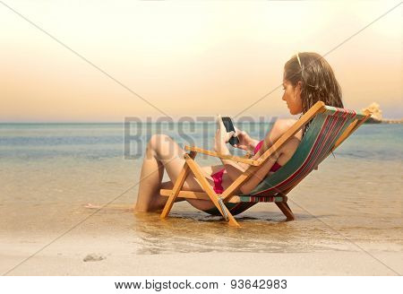 Young woman using her smart phone at the beach