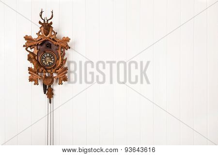 Wooden old cuckoo clock hanging on a white wall.