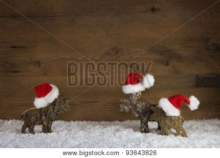 Three christmas reindeer of handmade wood with santa hats.