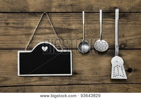 Wooden old kitchen background with old kitchenware, blackboard and spoons for cooking fans.