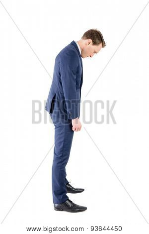 Defeated businessman looking at his shoes on white background