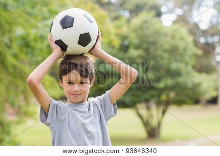 Smiling boy holding a soccer ball in the park on a sunny day