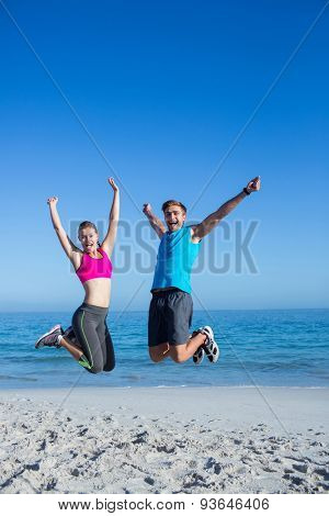 Happy couple jumping together at the beach