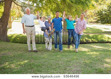Happy family playing together in the park on a sunny day