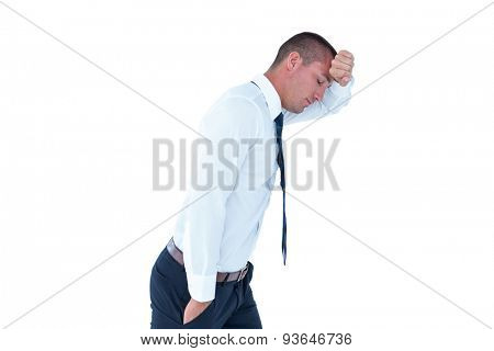 Worried businessman leaning on wall against a white background