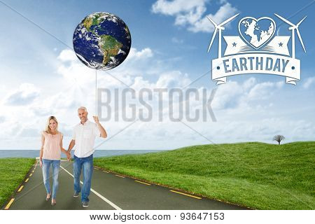 Happy couple walking holding hands against road leading out to the horizon