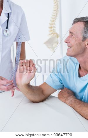 Doctor measuring wrist with goniometer in medical office