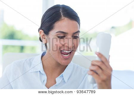 Businesswoman yelling at her phone in an office