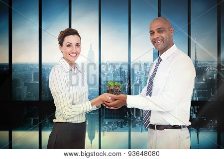 Business colleagues holding plant and looking at camera against room with large window looking on city